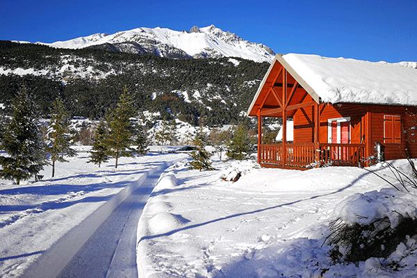 WiCa_Frankreich_0000_Camping-Municipal-Val-dAmbin-Schneebedecktes-Chalet-auf-dem-Campingplatz-mit-Blick-auf-die-Berge.png