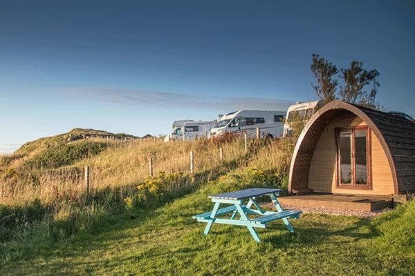 inselskye_Mag2020_0001_Camping-Loch-Greshornish-Club-Site-----Mobilheim-mit-Picknicktisch-aussen-und-Wohnmobile-auf-dem-.png