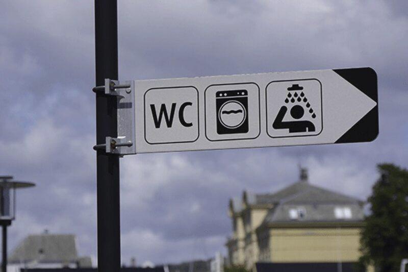 Ein Schild, das den Weg zur Toilette zeigt.