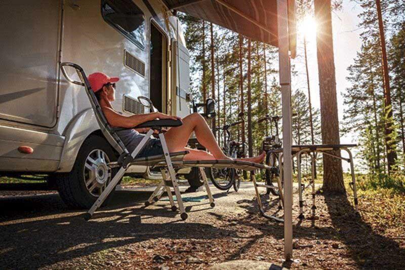 Frau im Campingstuhl vorm Wohnmobil.
