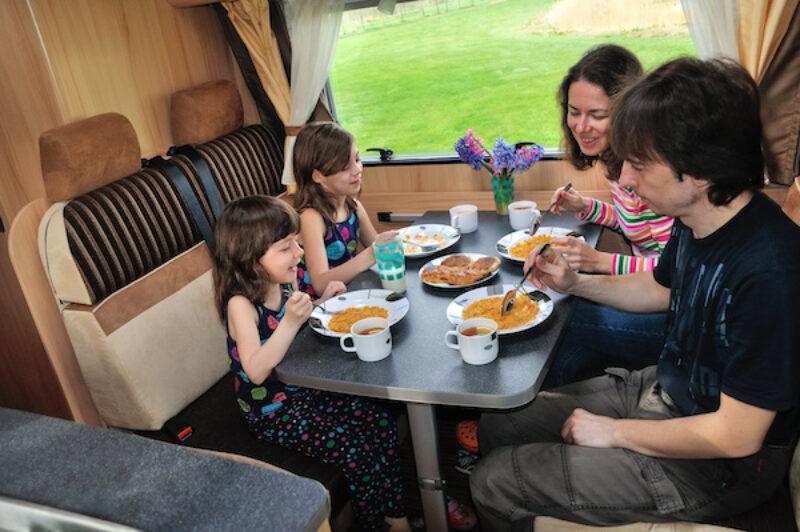 Familie im Wohnmobil am Tisch.