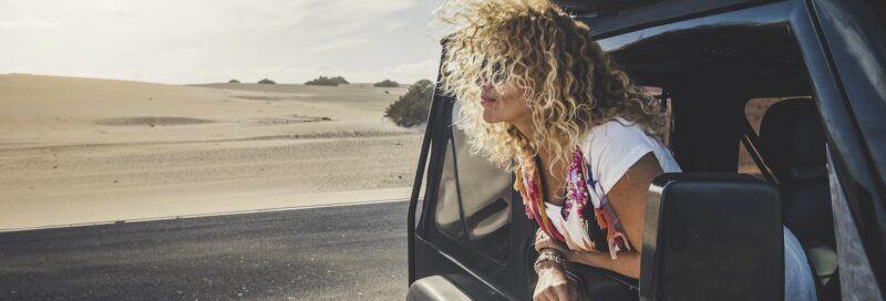 Eine Frau guckt aus einem Jeep heraus.