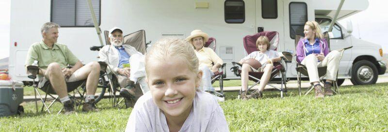 Eine Familie vor einem Wohnmobil.
