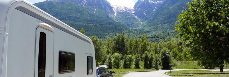 Wohnwagen mit Zugfahrzeug vor Bergpanorama