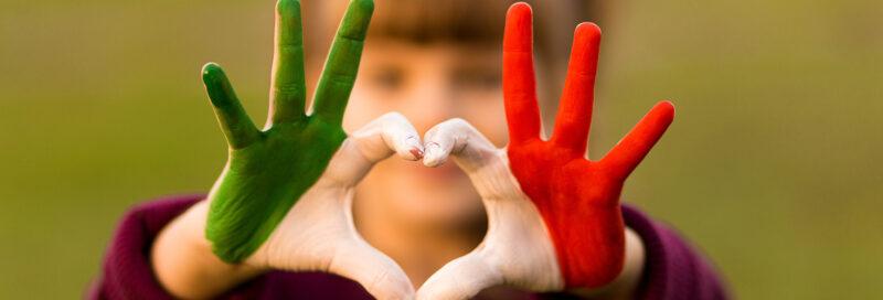 Mädchen zeigt Handherz mit Italienischer Flagge