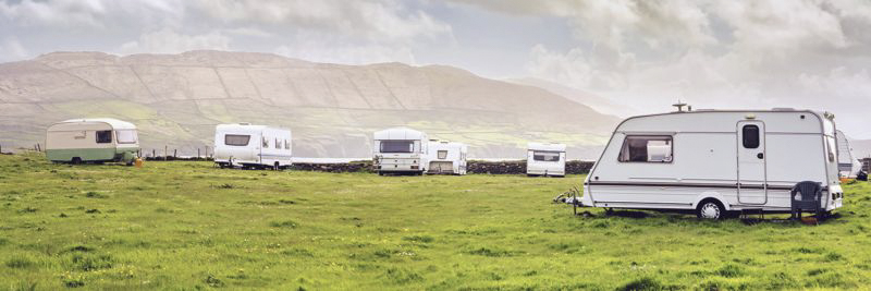 Mehrere Wohnwagen stehen auf einer Wiese mit Bergpanorama