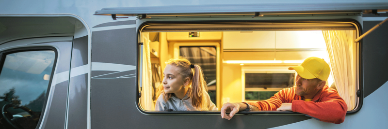 Vater schaut mit Kind aus Fenster des Wohnmobils