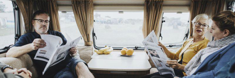 Mehrere Personen sitzen im Wohnwagen und lesen Zeitungen