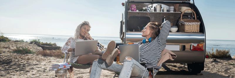 Zwei Personen sitzen mit Computer vor Mini-Wohnwagen