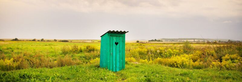 Hölzerne Toilette auf einer grünen Wiese