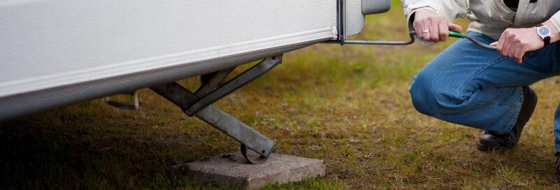Person schraubt Stellstütze aus dem Wohnwagen zur Absicherung