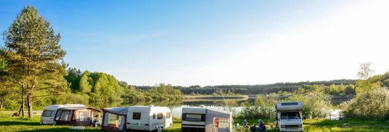 Wohnmobile und Wohnwagen auf dem Campingplatz am See