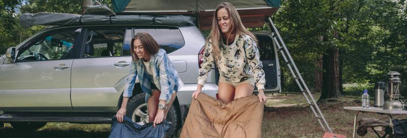Camper mit Autodachzelt auf dem Campingplatz