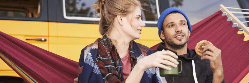 Pärchen sitzt vor Campingbus in Hängematte