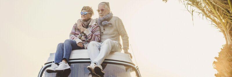 Ein älteres Paar sitzt auf dem Dach eines Campingbusses.