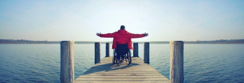 Ein Rollstuhlfahrer auf einem Steg in der Sonne.
