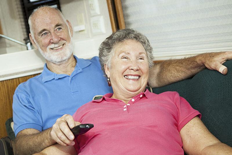 Älteres Pärchen schaut Fernsehen im Campervan
