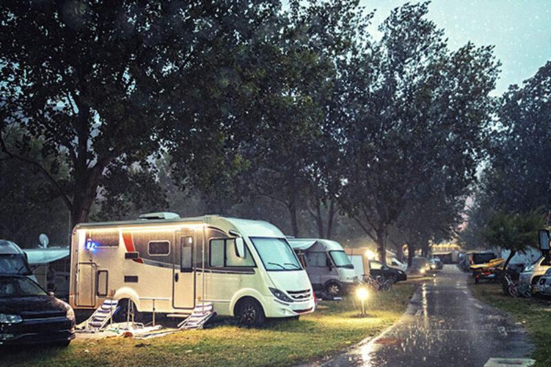 Wohnmobil steht bei Regen auf einem Stellplatz