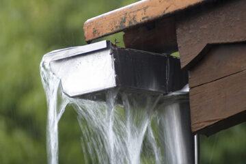 Regenrinne an einem Holzhäuschen läuft über