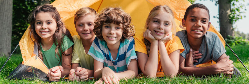 Kinder zelten in einem Zelt auf einem Campingplatz