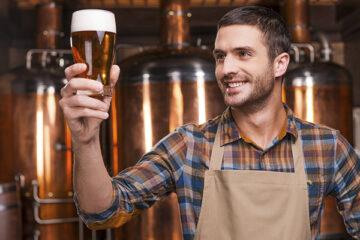 Brauer hält frisches Bier in der Hand und lächelt