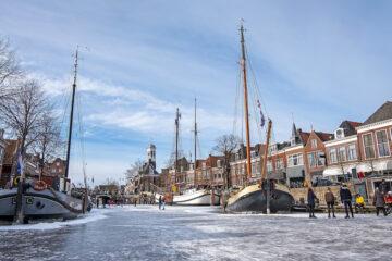 Eisskaten auf dem zugefrorenen Kanal in Dokkum