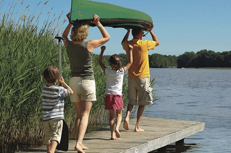 Familie trägt ein Kanu ins Wasser