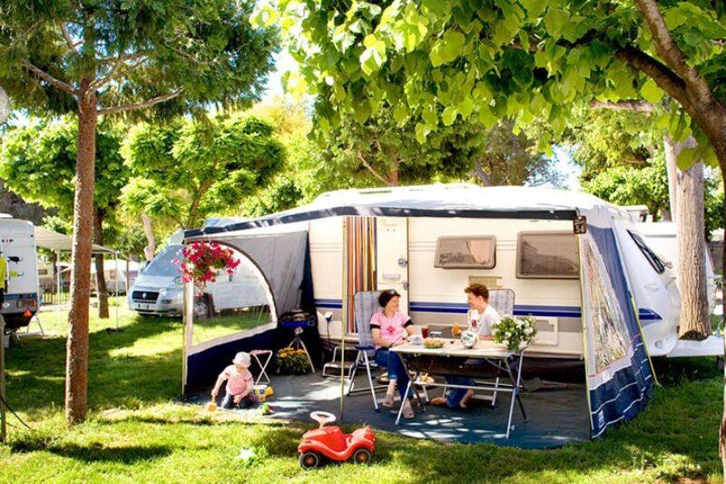 Camper sitzen vor dem Wohnmobil im Schatten der Markise