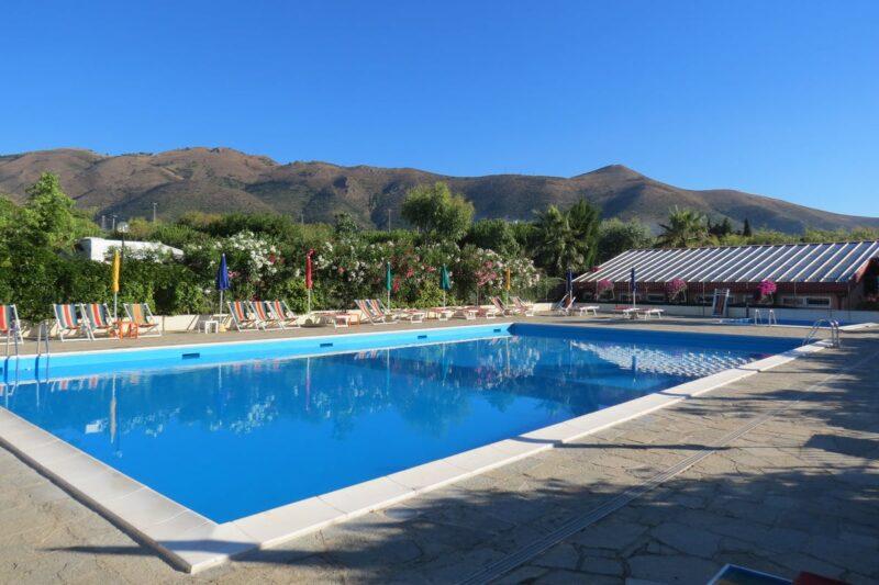 Swimmingpool mit Liegestühlen und Sonnenschirmen