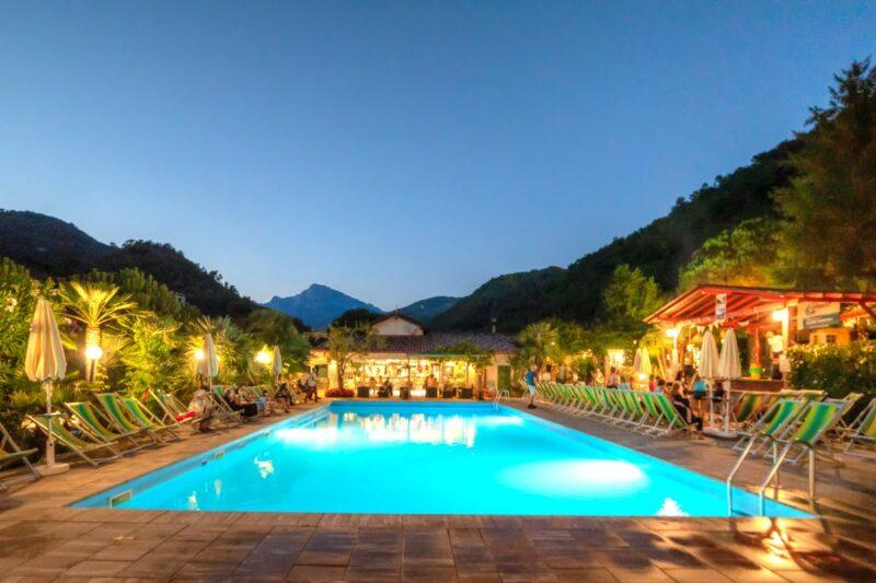 Poolbereich mit Liegestühlen und Beleuchtung am Abend auf dem Campingplatz