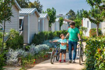 Camper mit Fahrrädern auf dem Campingplatz mit Mobilheimen