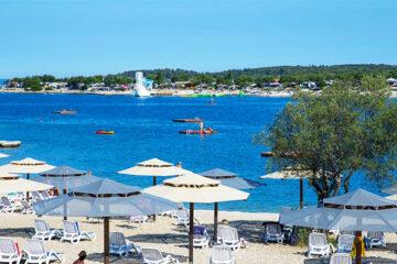 Strand vom Campingplatz-am-Mittelmeer-mit Sonnenschirmen und Liegestühlen