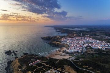 Luftaufnahme des Dorfes Zambujeira do Mar und des Strandes bei Sonnenuntergang, in Alentejo, Portugal