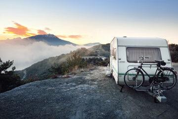 Wohnwagen-mit-dem-Fahrrad-in-den-Alpen-bei-Sonnenaufgang