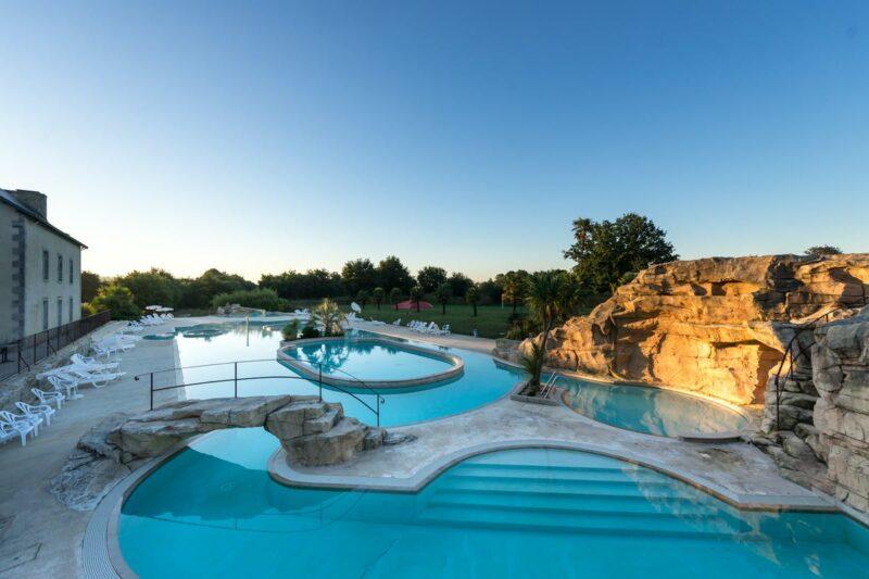 Blick auf Pool mit Planschbecken und Liegestühlen in der Abendsonne