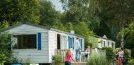 Gäste sitzen auf der Terrasse und spielen Ball auf dem grünen Rasen vor dem Mobilheim