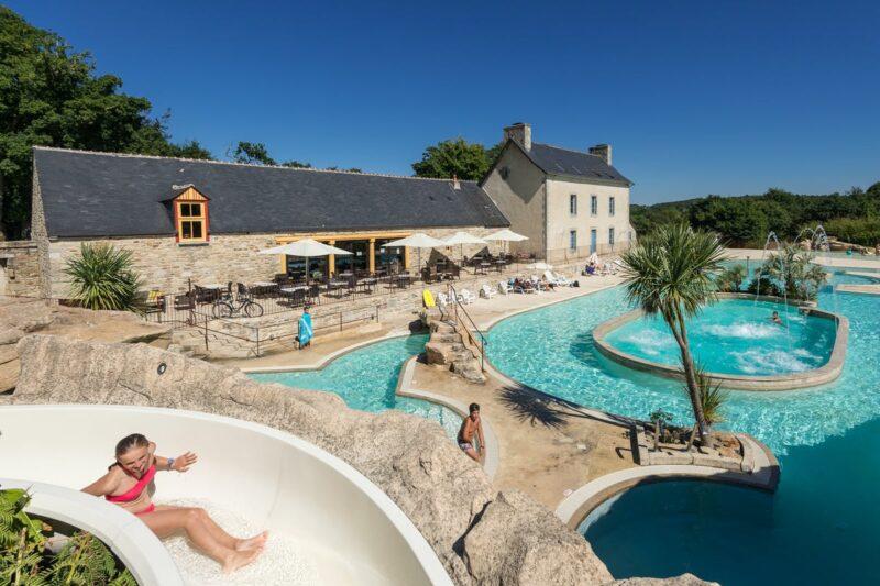 Poolbereich mit Wasserrutsche und Liegestuehlen auf dem Campingplatz