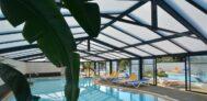 Indoor und Outdoor-Pool vom Campingplatz mit Liegestühlen in der Sonne