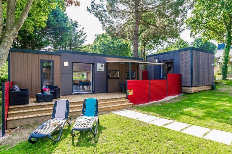 Mobilheim vom Campingplatz mit Veranda und Liegestühlen auf grüner Wiese