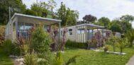 Mobilheime vom Campingplatz mit Veranden auf grüner Wiese