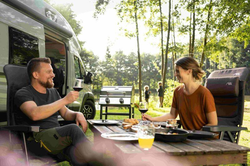 Ein Paar trinkt Wein neben dem Campervan und dem Grill
