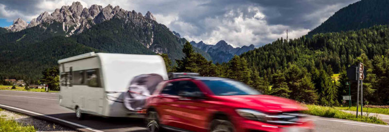 Zugwagen mit Wohnwagen vor Bergpanorama