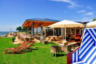 Camping-Wulfener-Hals----Liegestuehle-und-Esstische-auf-der-Terrasse-vom-Restaurant-auf-dem-Campingplatz-groß