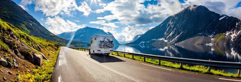 Wohnwagen auf Landstraße mit Bergpanorama